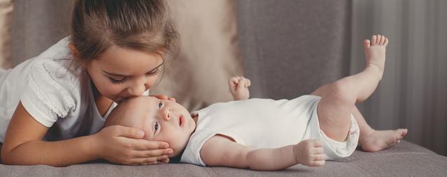 niña besando a bebe